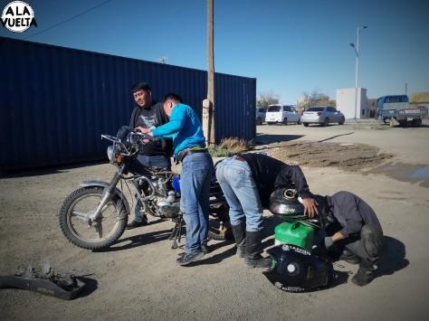 Cinco personas trabajan en la reparación del tanque de nafta de la moto de Germán.